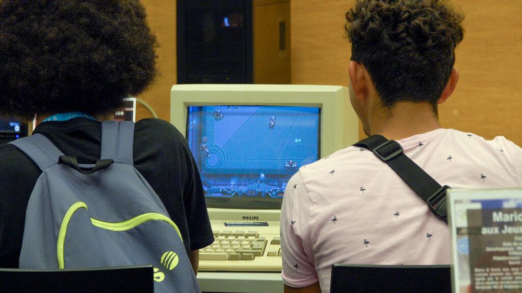 Deux visiteurs jouent à Speeball 2 (1990) sur un ordinateur Amiga 500 pendant la Nuit des Musées 2019 au Musée Bolo